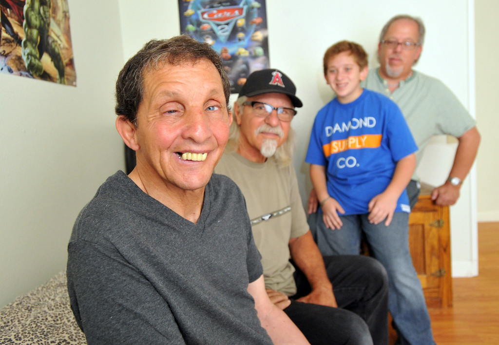 Description of . Gary Borack, 58, left, is joined by his brothers, Robert, center, and John and nephew, Michael, 11, at his group home in Mission Viejo on Wednesday June 26, 2013. Gary Borack, who was diagnosed with severe mental retardation at the age of 5, recently transitioned out of Lanterman Developmental Center in Pomona about 9 months ago, and is living successfully in the group home. (SGVN/Staff Photo by Keith Durflinger)