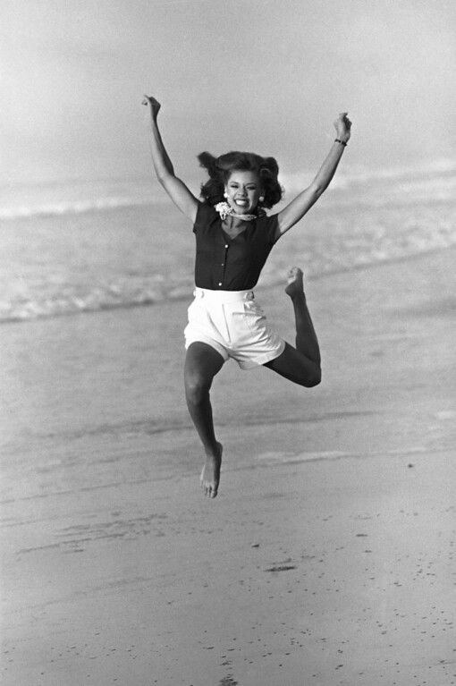 Description of . Vanessa Williams, Miss America for 1984, jumps for photographers on the beach in Atlantic City, New Jersey, Sept. 19, 1983. She is the first black Miss America in the pageant's history. (AP Photo)