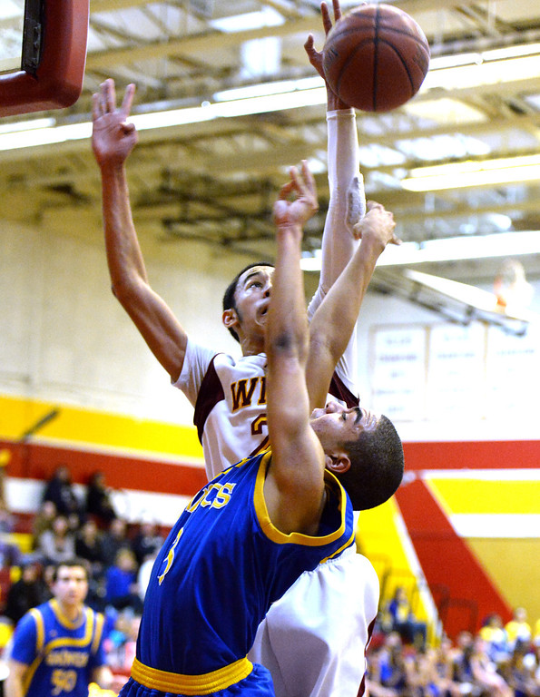 Description of . Wilson's Kevin Price (21) blocks the shot of San Dimas' Greyson McGee (C) (3) in the first half of a prep basketball game at Wilson High School in Hacienda Heights, Calif., on Friday, Jan. 31, 2014. (Keith Birmingham Pasadena Star-News)