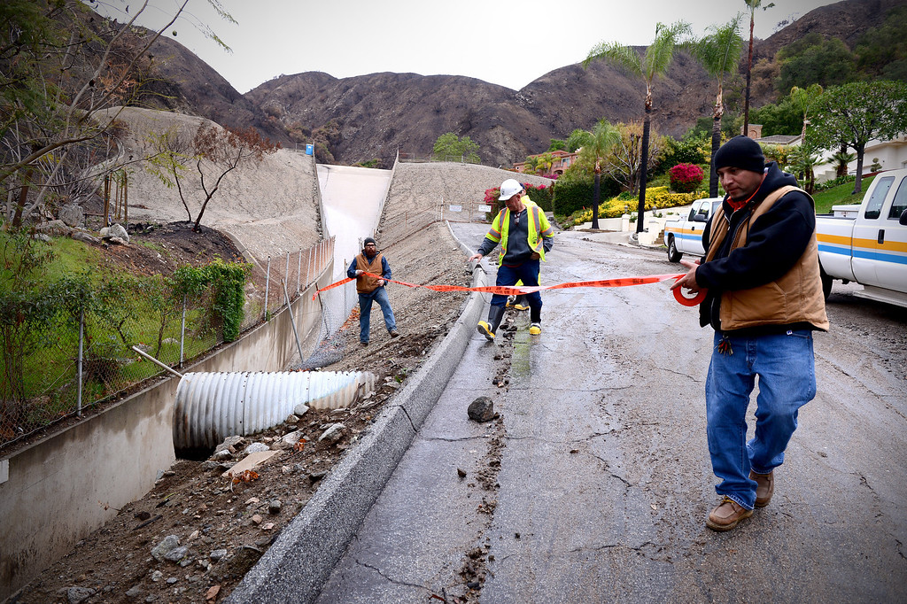 Description of . Los Angeles Public Works places tape where a fence was knocked down by mud along the access road to the Englewild Debris Basin in Glendora Saturday, March 1, 2014.  The debris basin, one of four key debris basins in the Colby Fire burn area, is about half full and is expected to hold out through the duration of the storm. (Photo by Sarah Reingewirtz/Pasadena Star-News)