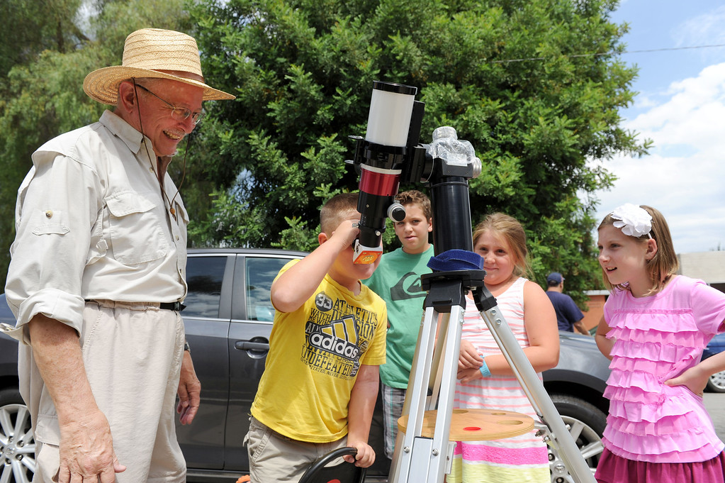 Description of . (John Valenzuela/Staff Photographer) Jim Sommer, a member of the San Bernardino Valley Amateur Astronomers, watches over Jacob Roth, 7, of Rancho Cucamonga, as he looks through a telescope at the sun, outside the A.K. Smiley Library in Redlands Thursday, August 29, 2013.  Tristan Chance, 10 (left), Charlie Roth, 9 (center), and Isabel Chance (right) wait to view the sun through Sommer's telescope.