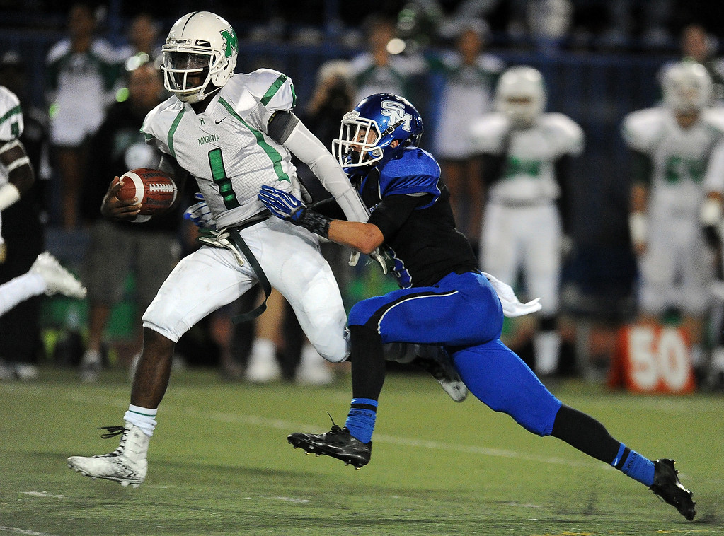 Description of . Monrovia quarterback Deshawn Potts (C) (1) runs for a first down as San Marino's Tyler Spitzer (3) tackles in the first half of a prep football game at Monrovia High School in Monrovia, Calif., on Friday, Nov. 8, 2013. 