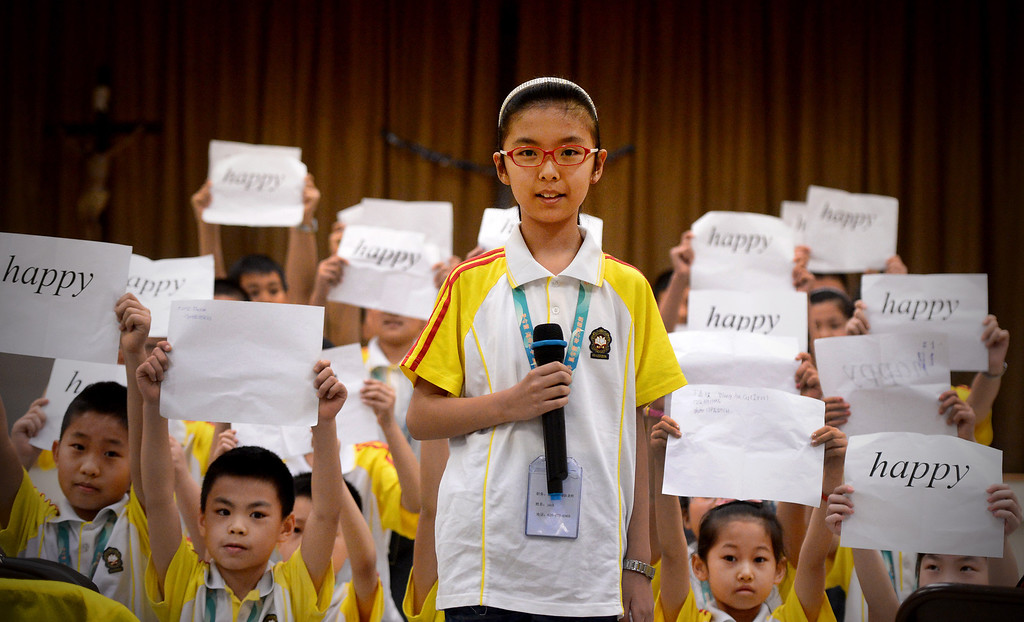 Description of . Zixio Wang, 9, of Harbin Normal University in China, leads her class in