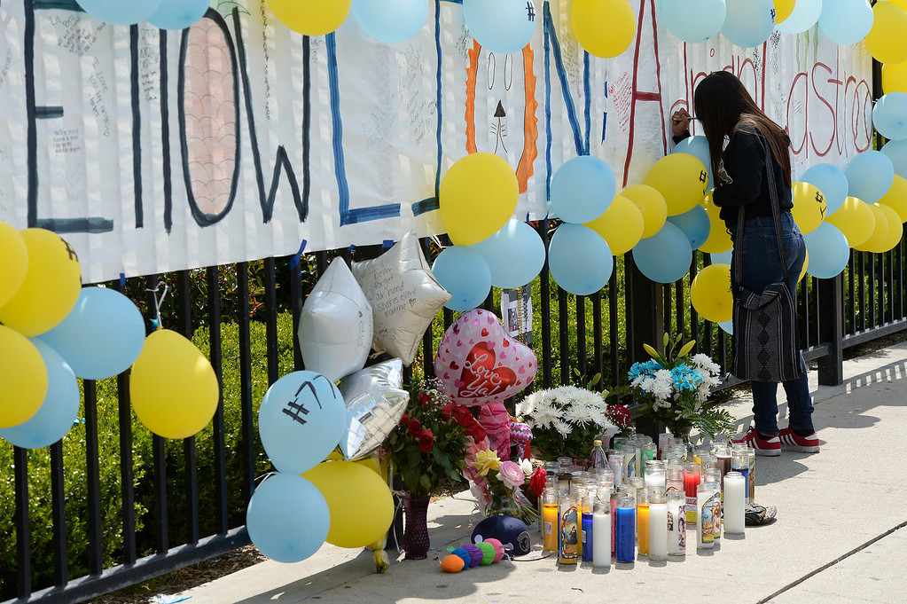 Description of . Sarah Baiza,15, writes on the memorial. Students at El Monte High School brought flowers, candles and other items in remembering Adrian Castro, a Senior student who was killed in bus crash in Northern California that took the lives of 10 people. El Monte, CA. 4/13/2014(Photo by John McCoy / Los Angeles Daily News)