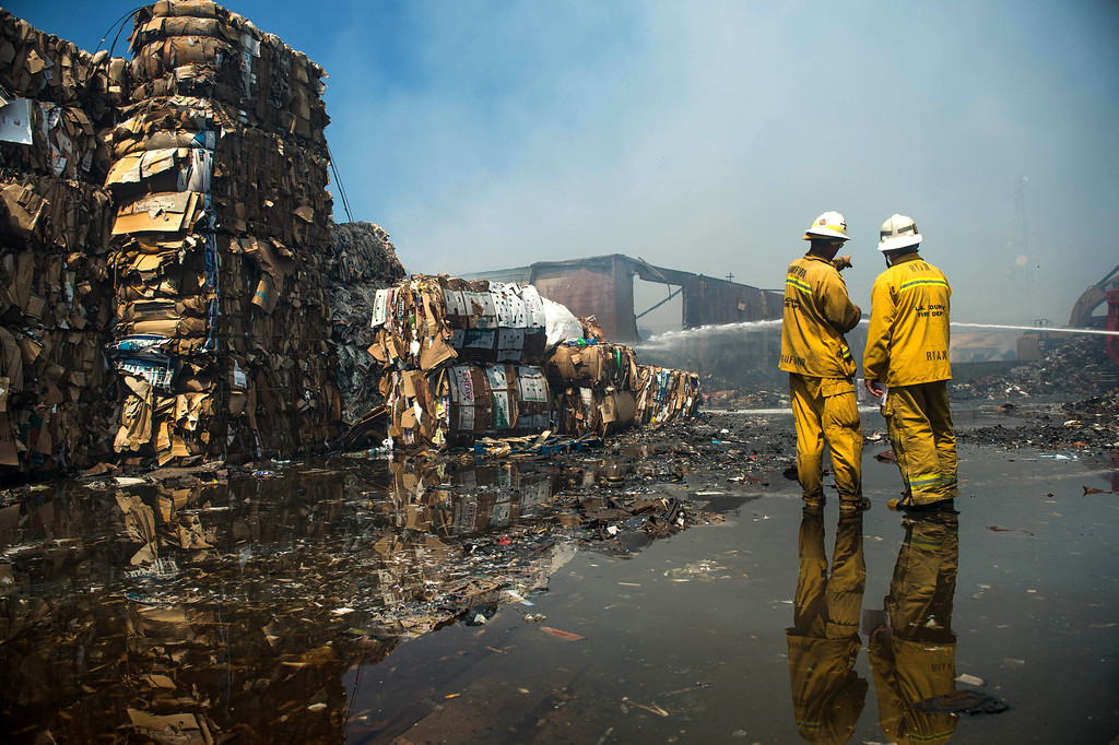 Description of . Firefighters mop-up a 5-alarm fire at a recycling center in the 14000 block of Marquardt Avenue in Santa Fe Springs on Friday morning, May 30, 2014. No injuries and the cause is under investigation. (Staff photo by Watchara Phomicinda/ Whittier Daily News)