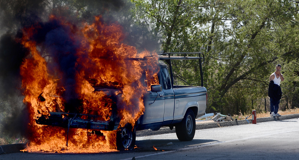 Description of . Marco Perez of Riverside stands behind his burning truck. Perez said he smelled gas coming from his truck and pulled over to the shoulder of the Vineyard Avenue offramp of the westbound 10. Cause of the fire is under investigation. (Rick Sforza/Inland Valley Daily Bulletin)