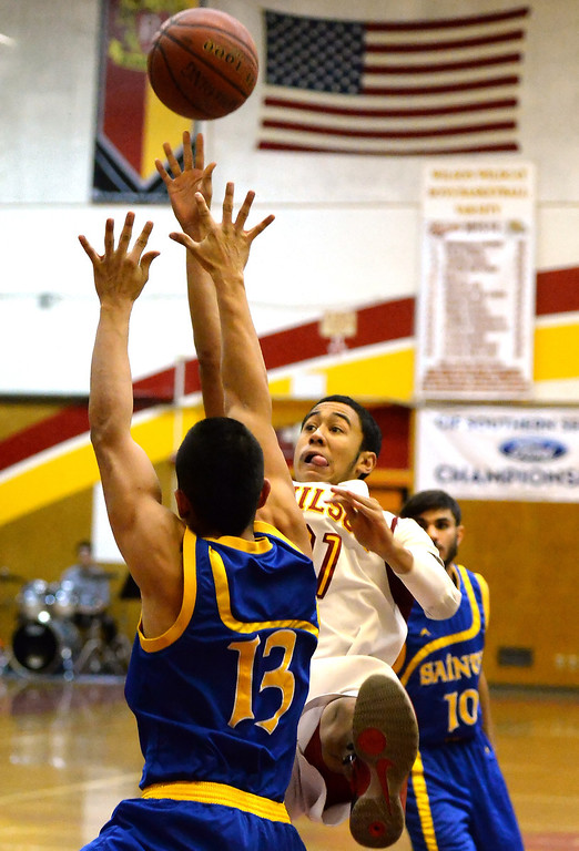 Description of . Wilson's Kevin Price (21) shoots over San Dimas' Tony Hugo (13) as Travis Schiewe (C) (10) looks on in the first half of a prep basketball game at Wilson High School in Hacienda Heights, Calif., on Friday, Jan. 31, 2014. (Keith Birmingham Pasadena Star-News)