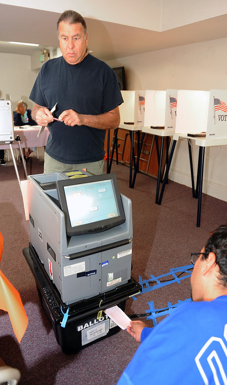 Description of . Robert Masin voted early and needed help from clerk Alan Martinez De Anda to place ballot in box directly sinch machine was not working. Early morning Election voting at First Baptist Church Fellowship hall on S. Encionitas Avenue in Monrovia Tuesday, June 3, 2014.(Photo by Walt Mancini/Pasadena Star-News)