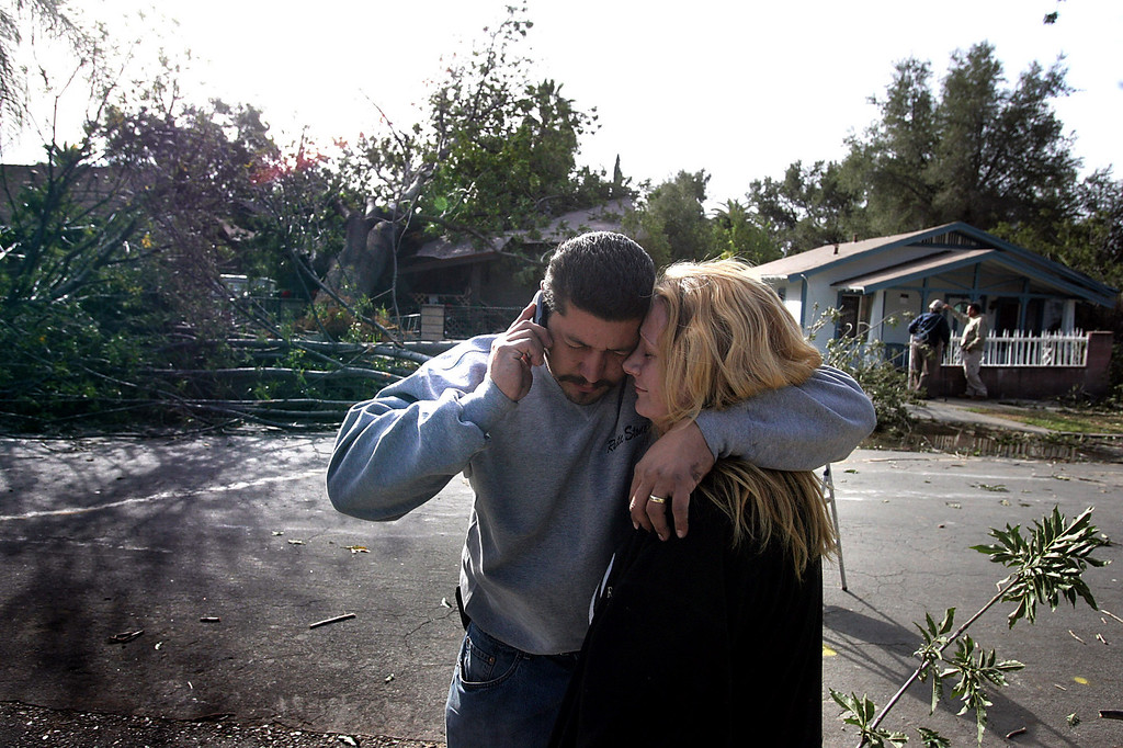 Description of . Carlos and Heather Flores stand before their home at 100 Cedar Street in Pasadena after a city tree crashed into their home trapping them and their three kids Thursday, December 1, 2011 as winds gusting up to 80 miles an hour whipped through the west San Gabriel Valley overnight. As many as 230,000 were reported without power and the city of Pasadena declared a state of emergency. The Flores family was helped by neighbors and their home was red tagged. (SGVN/Staff Photo by Sarah Reingewirtz/SXCITY)