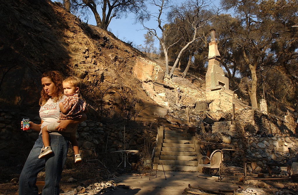 Description of . The GrandPrix fire started three days before the Old Fire.  It fed into the Old Fire. Ten years later, there are rumblings that it too was started by an arsonist. But to this day, its origins remain a mystery. With her nephew Clayton Barklow in tow Sarah Barklow passes by her devastated home in Palmer Canyon, Tuesday, Oct. 28, 2003, in Claremont. (Staff photo by Will Lester/Inland Valley Daily Bulletin)