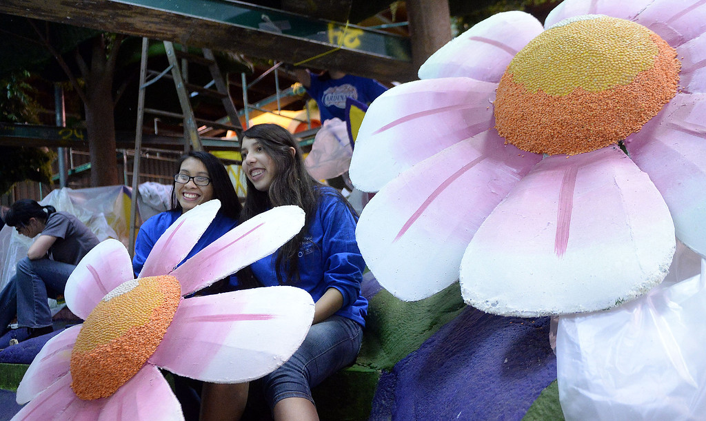 Description of . Joanna Scholtz, left, poses for a photograph with Summer Lopez-Colorado atop the City of Hope float during the final stages of preparation for the 2014 Rose Parade as a variety of seeds, bark, fruits and vegetables, grasses and of course, flowers are being applied to the floats by experienced professionals as well as hard working volunteers at the Rosemont Pavilion in Pasadena, Calif., on Saturday, Dec. 28, 2013.     (Keith Birmingham Pasadena Star-News)