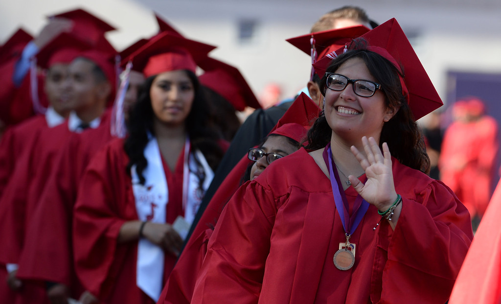 Description of . Students look toward the stands as family and friends cheer during the Whittier High School graduation at Whittier College in Whittier, Calif., on Wednesday, June 4, 2014.  (Keith Birmingham/Pasadena Star-News)