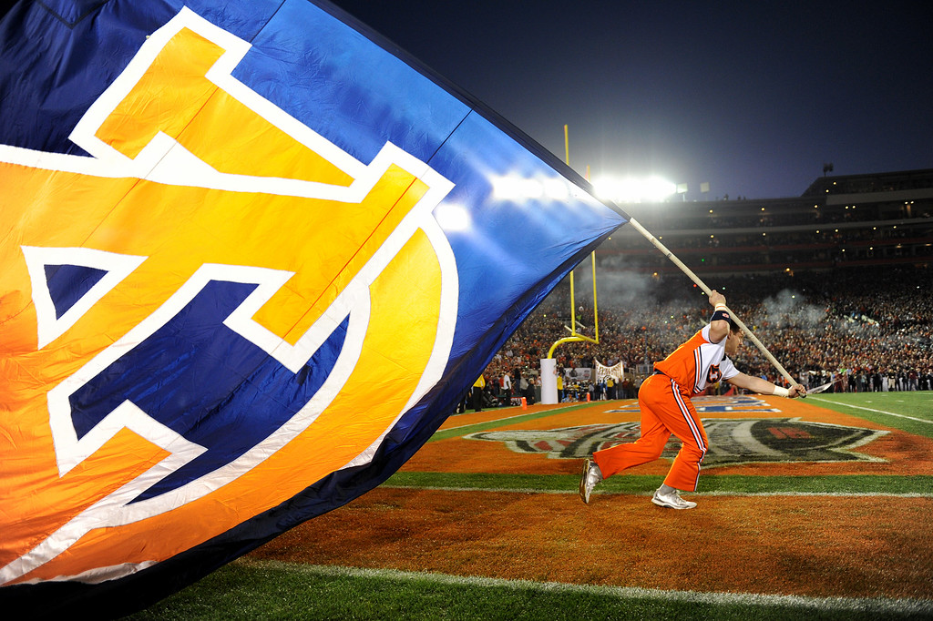 Description of . Auburn cheerleader Charles Jacobs starts his run with the flag before the start of the BCS national championship game at the Rose Bowl, Monday, January 6, 2014. (Photo by Michael Owen Baker/L.A. Daily News)