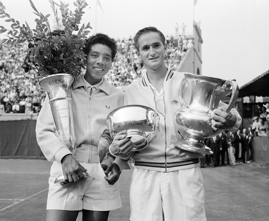 Description of . Althea Gibson, left, and Mal Anderson hold their trophies after their victories in the National Tennis Championships in Forest Hills, N.Y., Sept. 8, 1957.  (AP Photo/Harry Harris)