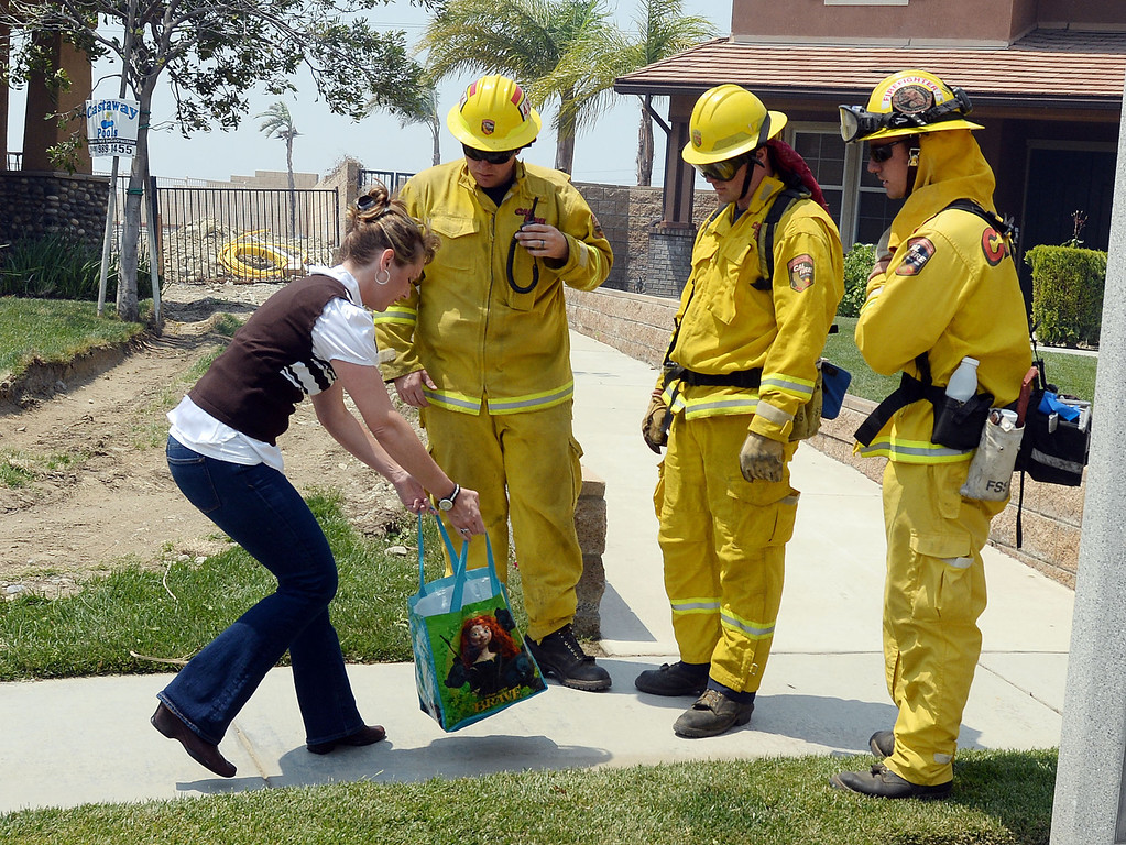 Description of . A Rancho Cucamonga resident gives water and snacks to firefighters Wednesday. Over 1,000 acres and over a 1,000 homes are under mandatory evacuation as the Etiwanda Fire burns in Rancho Cucamonga Wednesday April 30, 2014. Cause of the fire is unknown and is burning in areas which burned during the Grand Prix Fire in October 2003. (Will Lester/Inland Valley Daily Bulletin)