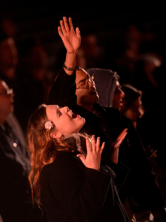 Description of . Lucy Rosta, 18, left, and Willard Hughs, right, both of Highland, sing a worship song during Easter Sunrise services at the Roosevelt Bowl in San Bernardino March 31, 2013.  Over 600 local Christians gathered to celebrate the resurrection of Jesus Christ.  (Photo by Gabriel Luis Acosta/The Sun)