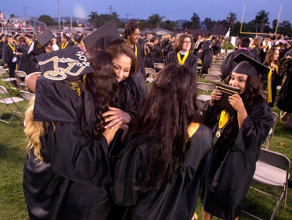 Description of . Northview High grads hug after their commencement ceremony at Covina District Field June 11, 2014.   (Staff photo by Leo Jarzomb/San Gabriel Valley Tribune)