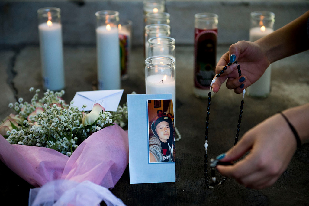 Description of . Justine Sarmiento, 17, places a rosary at a makeshift memorial for Cristopher Rossi, 16, outside his Duarte apartment on Tuesday, Dec. 24, 2013. Rossi was fatally shot outside his home Monday night. (Staff photo by Watchara Phomicinda/ San Gabriel Valley Tribune)