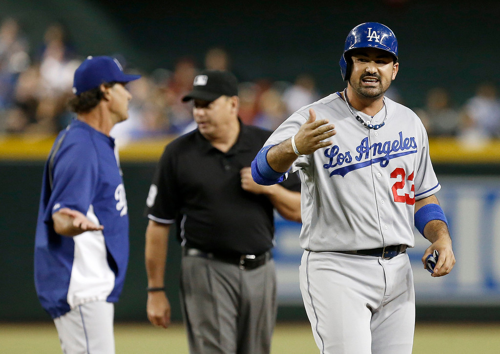 Description of . Los Angeles Dodgers' Adrian Gonzalez (23) keeps yelling after he is ejected for arguing a call in the sixth inning as Dodgers' manager argues with umpire Andy Fletcher during a baseball game against the Arizona Diamondbacks on Wednesday, Sept. 18, 2013, in Phoenix. Diamondbacks won 9-4.   (AP Photo/Ross D. Franklin)
