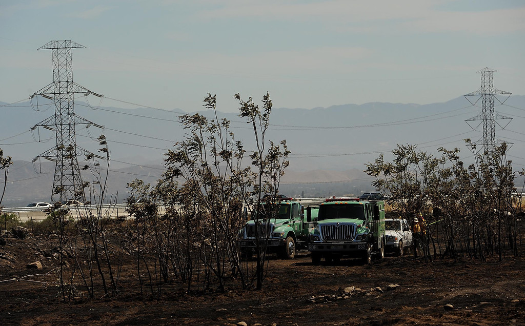 Description of . A view of fire crews working hot spots on land that burned in Mondays fire along the I-15 freeway near Sierra Avenue exit in North Fontana May 14, 2013.  GABRIEL LUIS ACOSTA/STAFF PHOTOGRAPHER.