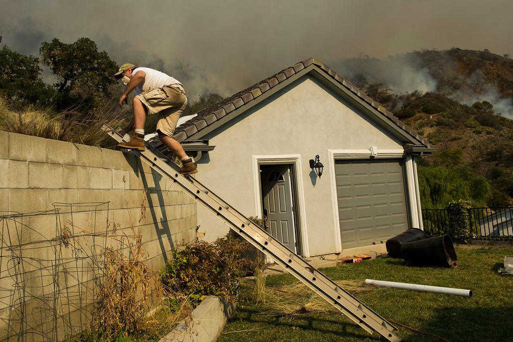 Description of . Mark Davis runs water hoes around his home to defend it from the wildfire burning on Hicrest Road in Glendora, Calif. on Thursday, Jan. 16, 2014. (Photo by Watchara Phomicinda/ San Gabriel Valley Tribune)