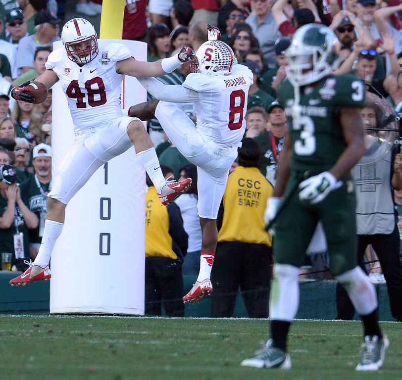 Description of . Stanford's Kevin Anderson (48) reacts with teammate Stanford safety Jordan Richards (8) after intercepting a pass and running for a touchdown as Michigan State wide receiver Macgarrett Kings Jr. (3) walks towards hid bench in the first half of the 100th Rose bowl game in Pasadena, Calif., on Wednesday, Jan.1, 2014. 
