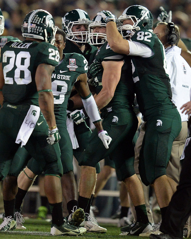 Description of . Michigan State's Kyler Elsworth #41 is mobbed by teammates after stoping Stanford's Ryan Hewitt #85 on 4th and 1 late in the 4th quarter during the 100th Rose Bowl game in Pasadena Wednesday, January 1, 2014. Michigan State defeated Stanford 24-20. (Photo by Hans Gutknecht/Los Angeles Daily News)