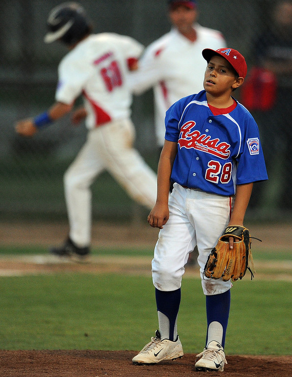 Description of . Azusa's starting pitcher Jason Nunez looks toward the outfield after giving-up a solo home run to La Verne's Noah Woodall (60) in the fifth inning of a championship Little League Section 3 championship baseball game at Homer Briggs Park on Wednesday, July 17, 2013 in Ontario, Calif. La Verne won 3-2 in 8 innings.   (Keith Birmingham/Pasadena Star-News)