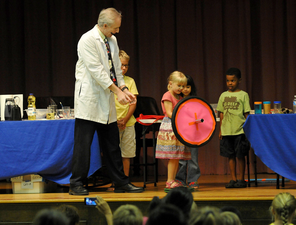 Description of . (John Valenzuela/Staff Photographer)  Rich Blagden of Achieve Science watches as Paige Zent 5, of Redlands, stands on  a rotating tray and holds onto a spinning wheel, causing her to move from side to side, during the Summer Reading Program's interactive science show at the Contemporary Club in Redlands, Tuesday, June 25, 2013.