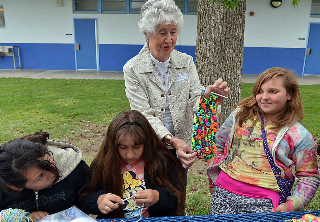Description of . Barbara Ferguson, standing, compliments Amelia Jones, 11, on her crochet work Wednesday May 7, 2014. Twice a week, for the past six years, fifth-graders at Lugonia Elementary School in Redlands have spent their lunch time crocheting. The