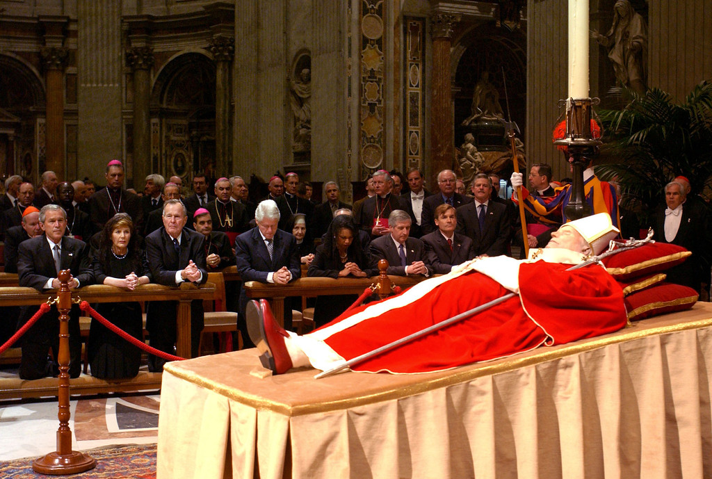 Description of . In this photo made available by the Vatican newspaper Osservatore Romano, front row from left, US President George W. Bush, his wife Laura, his father former President George H.W. Bush, former President Bill Clinton and Secretary of State Condoleezza Rice, kneel  by the body of late Pope John Paul II as he lies in state inside St. Peter's Baslica, at the Vatican, Wednesday, April 6, 2005. They  will attend his funeral on Friday. (AP Photo/Osservatore Romano,ho)