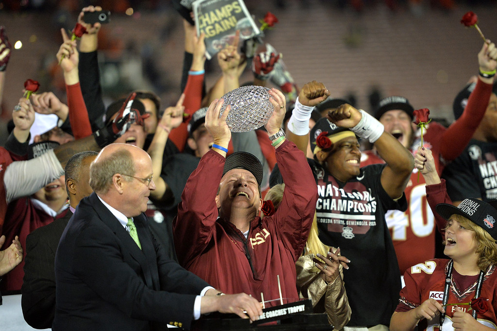 Description of . Florida State head coach Jimbo Fisher hoists the championship trophy after beating Auburn 34-31 in the BCS national championship game at the Rose Bowl, Monday, January 6, 2014. (Photo by Michael Owen Baker/L.A. Daily News)
