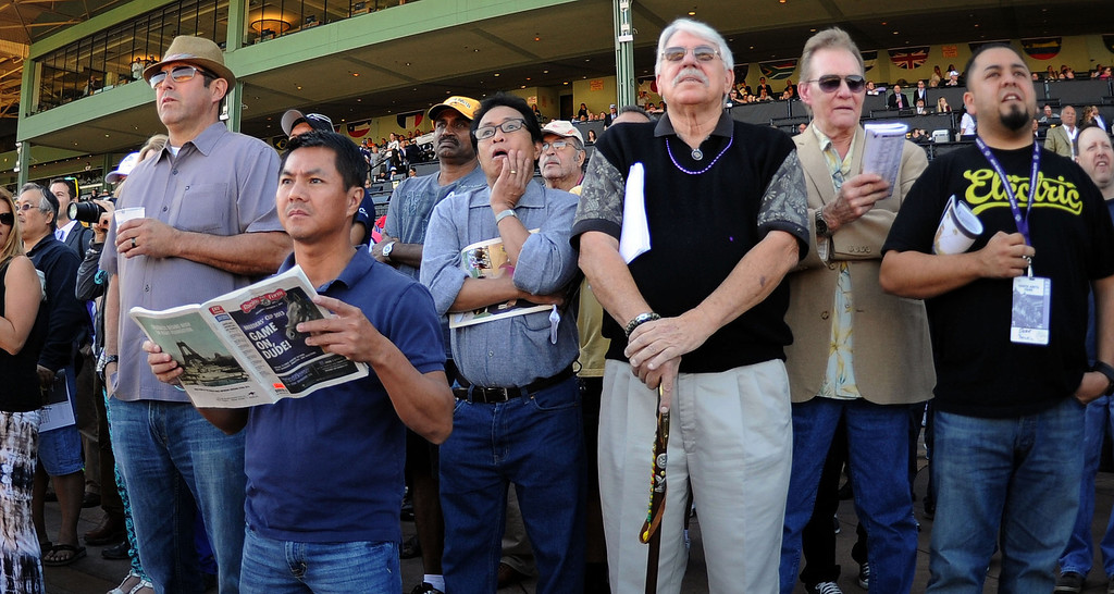 Description of . Fans watch the first race of the day during the Breeders' Cup at Santa Anita Park in Arcadia, Calif., on Saturday, Nov. 2, 2013. 