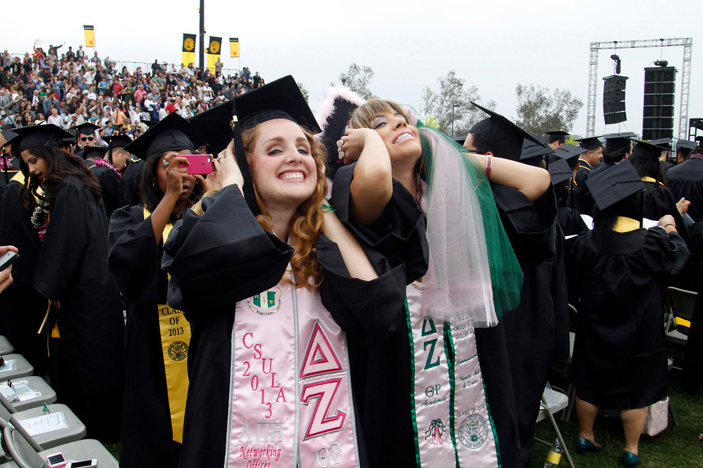 Description of . Megan Ryan, 22, left, and Brittany Rios, 22, both of Los Angeles, during the California State University, Los Angeles, Sixty-Sixth Graduate and Undergraduate Commencement Ceremony, at California State University Athletic Stadium, in Los Angeles, Saturday, June 15, 2013. (Correspondent Photo by James Carbone/SXCITY)