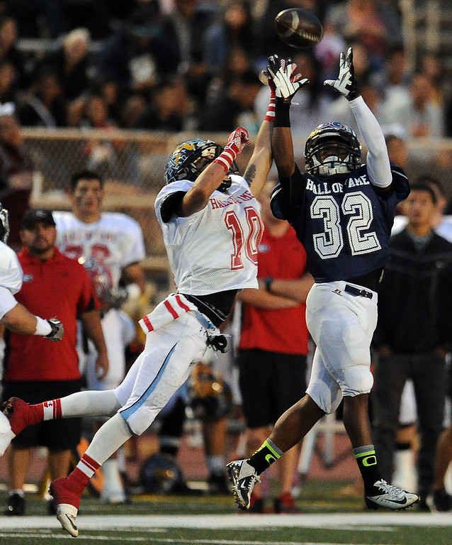 Description of . West's Ezra Broadus (32) (Alhambra) catches a pass in front of East's Jesus Arteaga (10) ( Azusa) in the first half of the annual East vs. West San Gabriel Valley Hall of Fame all-star football game at West Covina High School on Friday, May 17, 2013 in West Covina, Calif. 