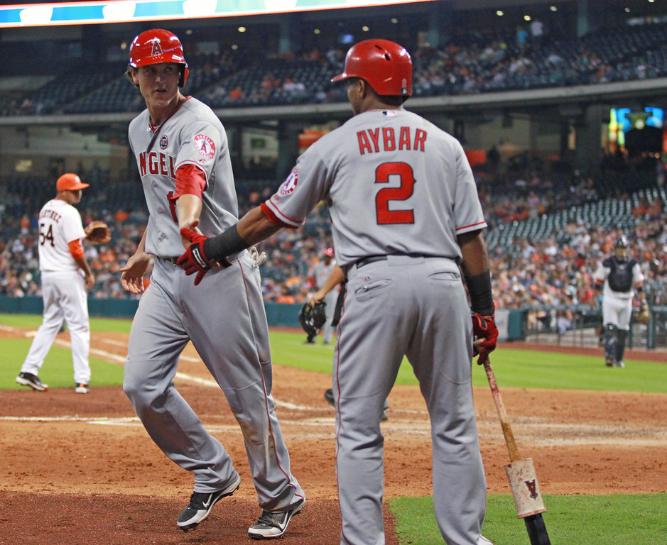 Description of . Los Angeles Angels' Grant Green, left, is congratulated by Erick Aybar after scoring on a wild pitch in the seventh inning of a baseball game against the Houston Astros on Saturday, Sept. 14, 2013, in Houston. (AP Photo/Eric Christian Smith)