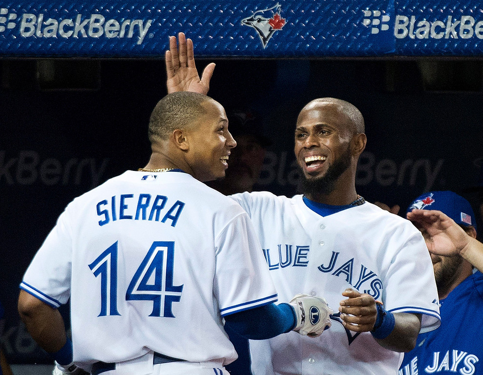 Description of . Toronto Blue Jays' Jose Reyes, right, celebrates with teammate Moises Sierra, left, after Sierra hit a triple and then advanced to home plate to score a run after there was an error at third base while playing against the Los Angeles Angels during fourth-inning AL baseball game action in Toronto, Wednesday, Sept. 11, 2013. (AP Photo/The Canadian Press, Nathan Denette)