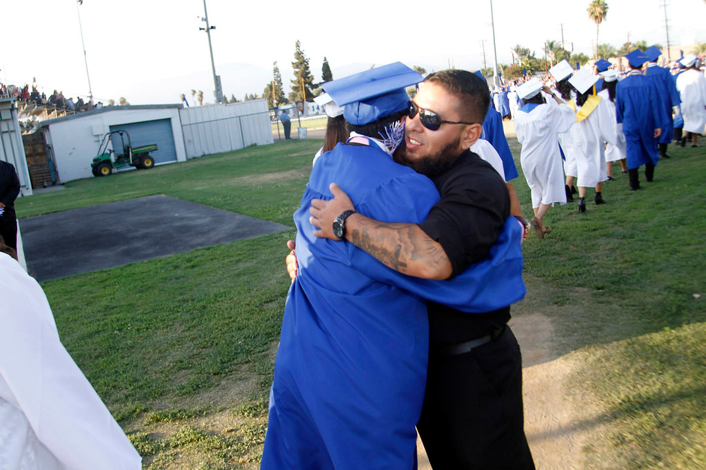 Description of . El Monte High School coach, David Parades, right, hugs graduates during the El Monte High School Class of 2014 Commencement Ceremony, at El Monte High School's Football Stadium in El Monte, CA., Wednesday, June 11, 2014.  (Photo by James Carbone for the San Gabriel Valley Tribune)