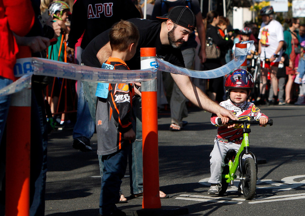 Description of . Chris Buscaglia, left, redirects son Enzo, 3, back onto the course during the public race portion of the Redlands Bicycle Classic on Saturday, April 5, 2014 in Redlands, Ca. (Photo by Micah Escamilla for the Redlands Daily Facts)
