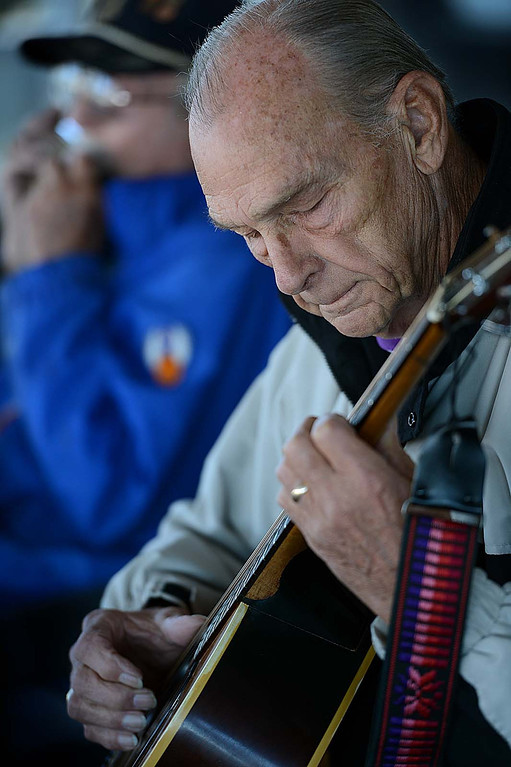 Description of . John Stoneking, 81, plays the guitar with a group of fellow World War II Veterans. The Redlands Airport Philharmonic gather each Wednesday in the lobby of the Redlands Airport to share stories, coffee, donuts and