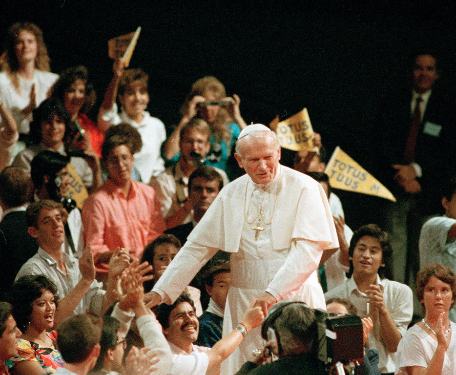 Description of . Pope John Paul II walks among young people at the Universal Amphitheatre in Los Angeles, Calif., Sept. 15, 1987.  The pontiff addressed the group along with satellite viewers in Portland, Denver and St. Louis. (AP Photo/Bob Galbraith)