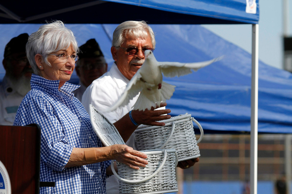 Description of . Bobolene Pope, left, and Edward Molina, release doves during the Vietnam Veterans Memorial