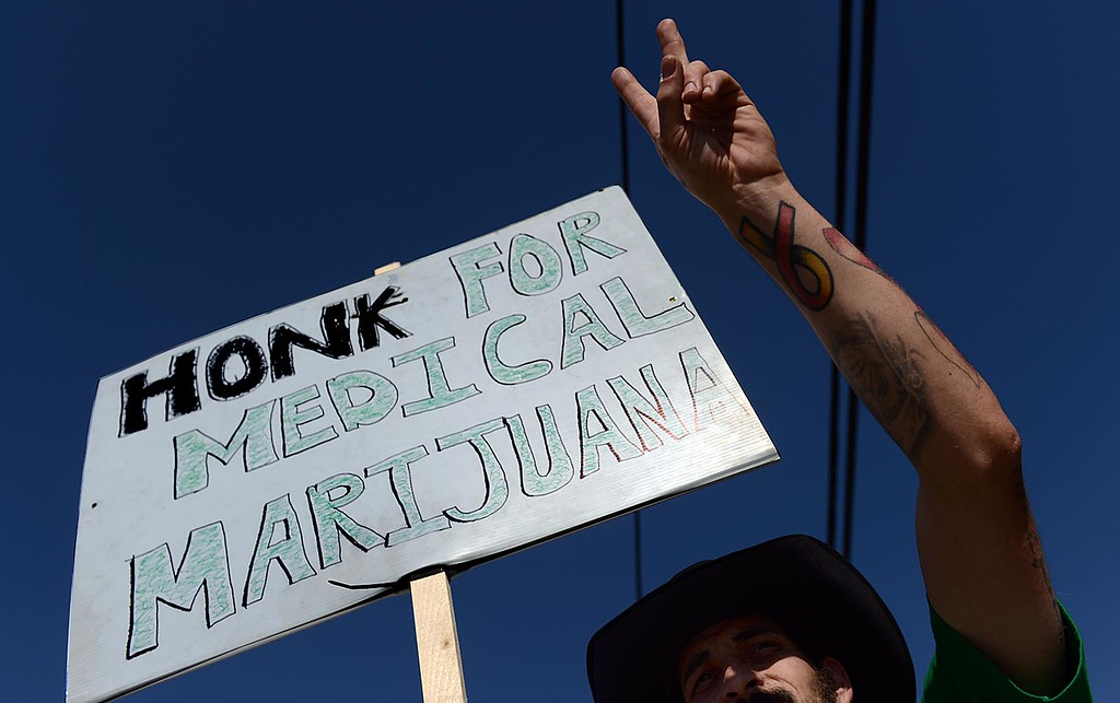 Description of . George Lanzas, 33 of Hesperia and manager of Doc Holliday's Collective, in Mentone, joins supporters in protest of the closure of the medical marijuana dispensary Monday August 12, 2013.  (Staff photo by Rick Sforza)
