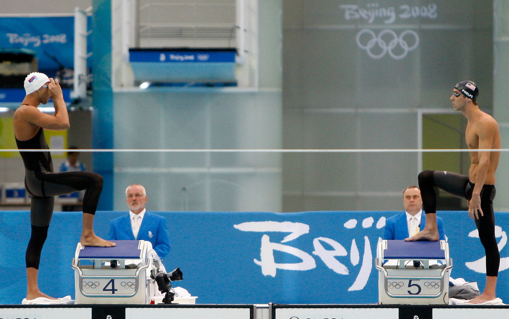Description of . In this Aug. 16, 2008 file photo, United States' Michael Phelps, right, and Serbia's Milorad Cavic face each other before the start of the final of the men's 100-meter butterfly during the swimming competitions in the National Aquatics Center at the Beijing 2008 Olympics in Beijing. (AP Photo/Mark Baker/FILE)