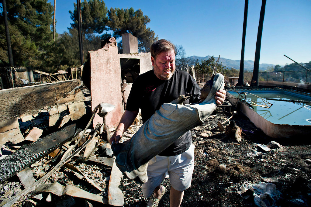 Description of . Greg Peterson saves an antique religious statue from the remains of his home after it was destroyed by the Colby Fire in Glendora on Friday morning, Jan. 17, 2014. Glendora residents return to their homes this morning after the mandatory evacuations were lifted. (Photo by Watchara Phomicinda/ San Gabriel Valley Tribune)