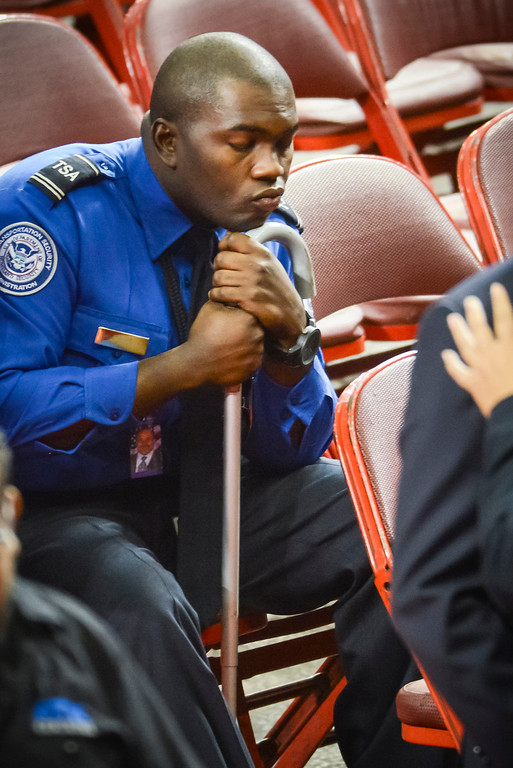 Description of . Wounded TSA officer Tony Grigsby sits after the memorial for slain TSA officer Gerardo Hernandez at the Los Angeles Sports Arena Tuesday, November 12, 2013.  A public memorial was held for Officer Gerardo who was killed at LAX when a gunman entered terminal 3 and opened fire with a semi-automatic rifle, Grigsby was wounded in the attack.  ( Photo by David Crane/Los Angeles Daily News )