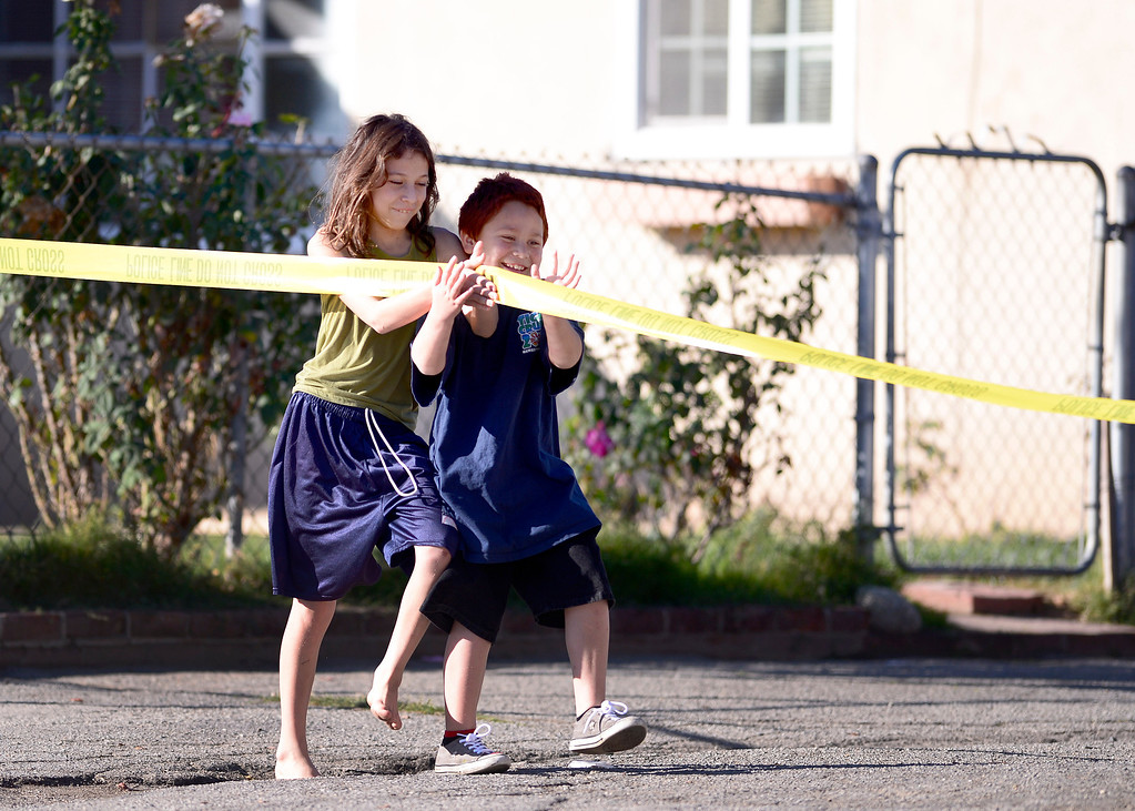 Description of . Children play with police tape not far from where Pomona Police detectives investigate the shooting of a teenage girl in the 1000 block of Laurel Avenue in Pomona Saturday, November 30, 2013.  The city has been plagued by violence, with 27 homicides this year. Police are offering $10,000 rewards for information leading to conviction in any of this year's unsolved killings. (Photo by Sarah Reingewirtz/Pasadena Star-News)