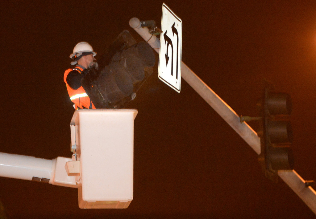 Description of . A city worker removes a signal light that was dangling from its wires at the intersection of Beach Booulevard and Lambert Road in La Habra on Friday March 28, 2014. (Staff Photo by Keith Durflinger/Whittier Daily News)