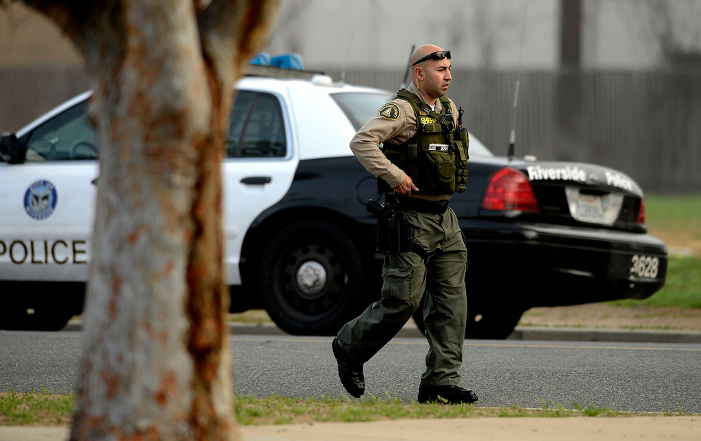 Description of . A Riverside County Sheriff Deputy takes a position on Washington Street near the intersection of Arlington and Magnolia Avenues in Riverside  where fugitive Christopher Dorner shot two Riverside officers killing one in Riverside February 7, 2012.  Arrests warrants for Christopher Dorner  have been released to the public by the County of Riverside. (Photo by Gabriel Luis Acosta/The Sun)