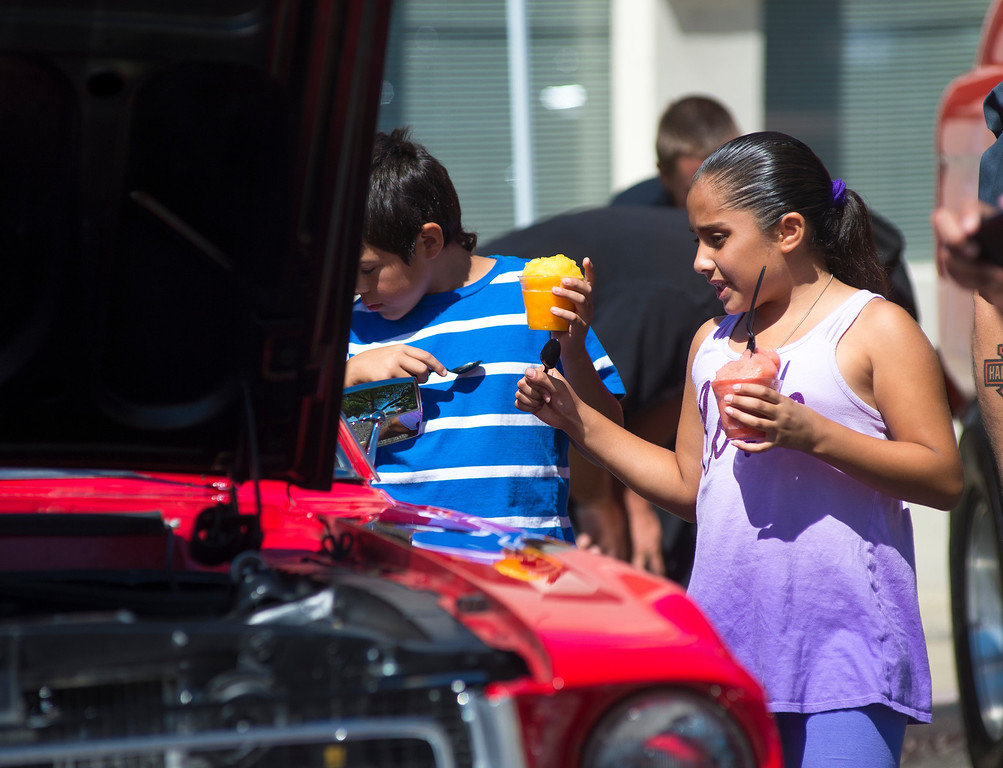 Description of . IDB-L-DBROUTE66-SUN-02 Siblings Adrien Moreno, 10, and Laryssa Perez, 9, of Upland, enjoy a cold treat as they check out the classic cars that  line Euclid Ave in Ontario, on the last day of the  Route 66 Cruisin' Reunion, on Sunday, September 22, 2013. (photos by Frank Perez for the Daily Bulletin)